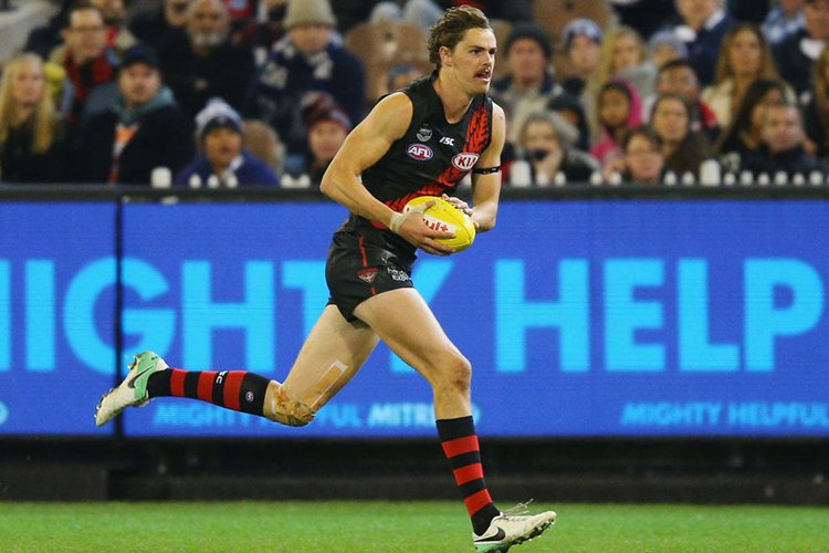 JOE DANIHER of the Bombers runs with the ball during the AFL match between the Essendon Bombers and the Geelong Cats at MCG in Melbourne, Australia.