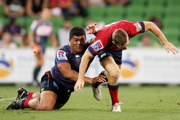 ames Tuttle of the Reds passes the ball whilst being tackled by JORDAN UELESE of the Rebels during the Super Rugby match between the Melbourne Rebels and the Queensland Reds at AAMI Park in Melbourne, Australia.