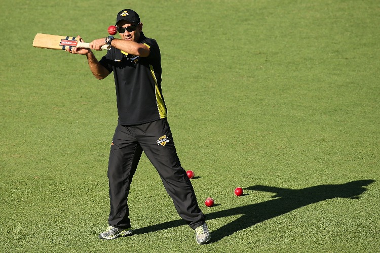 Warriors coach JUSTIN LANGER hits balls for catching practice at the change of innings during the Sheffield Shield match between the Western Australia Warriors and the South Australia Redbacks at WACA Perth, Australia.