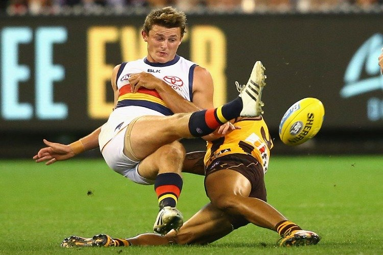 MATT CROUCH of the Crows kicks whilst being tackled by Cyril Rioli of the Hawks during the AFL match between the Hawthorn Hawks and the Adelaide Crows at MCG in Melbourne, Australia.