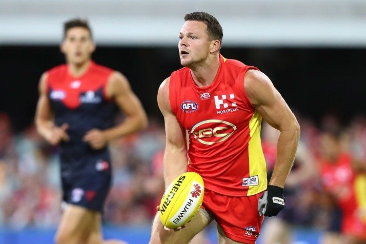 STEVEN MAY of the Suns handballs during the AFL match between the Gold Coast Suns and the Melbourne Demons at The Gabba in Brisbane, Australia.