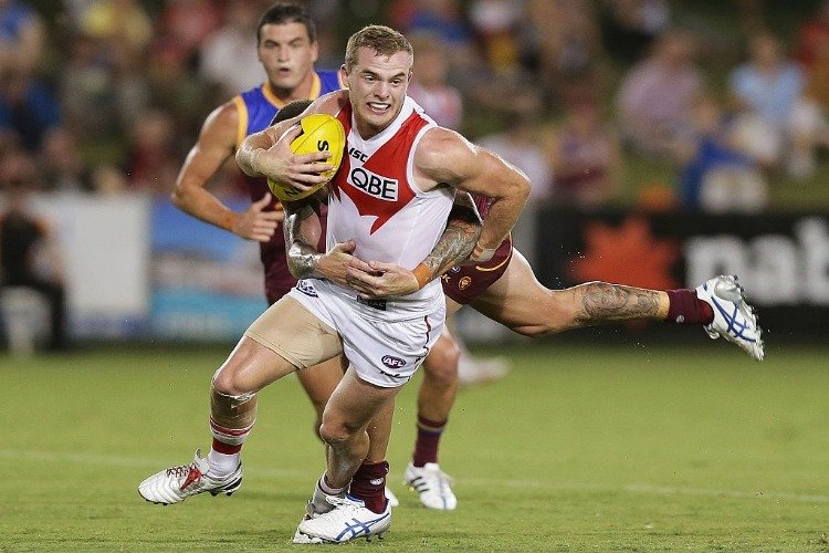 TOM MITCHELL of the Swans is tackled by Claye Beams of the Lions during the NAB Challenge AFL match between the Sydney Swans and the Brisbane Lions at Coffs Harbour International Stadium in Coffs Harbour, Australia.