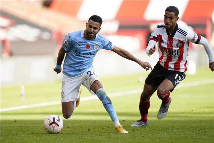 RIYAD MAHREZ of Manchester City is challenged by Max Lowe of Sheffield United during the Premier League match at Sheffield, England. Photo by Tim Keeton - Pool/Getty Images