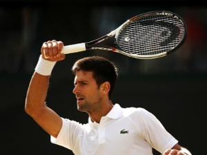 NOVAK DJOKOVIC of Serbia plays a forehand against Tomas Berdych of The Czech Republic in the Wimbledon Lawn Tennis Championships at the All England Lawn Tennis and Croquet Club in London, England.