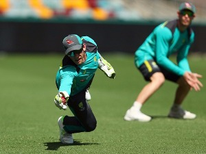 TIM PAINE dives for a catch during an Australia training session at The Gabba in Brisbane, Australia.