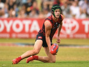 ANGUS BRAYSHAW of the Demons handballs during the AFL match between the Melbourne Demons and the Adelaide Crows at Traeger Park in Alice Springs, Australia.