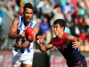 DANIEL WELLS of the Kangaroos handballs during the AFL match between the North Melbourne Kangaroos and the Melbourne Demons at Blundstone Arena in Hobart, Australia.