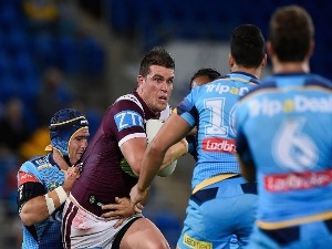 DARCY LUSSICK of the Sea Eagles is tackled during the NRL match between the Gold Coast Titans and the Manly Sea Eagles at Cbus Super Stadium in Gold Coast, Australia.