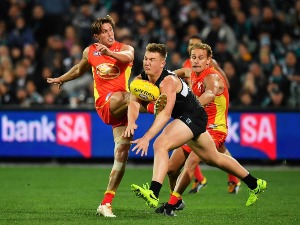 DARCY MACPHERSON of the Suns kick is smothered by Ollie Wines of the Power during the AFL match between the Port Adelaide Power and the Gold Coast Suns at Adelaide Oval in Adelaide, Australia.