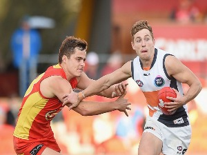 DEVON SMITH of the Giants takes on the defence during the AFL match between the Gold Coast Suns and the Greater Western Sydney Giants at Metricon Stadium on the Gold Coast, Australia.