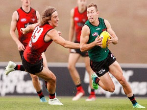 DEVON SMITH of the Bombers runs with the ball under pressure from Kobe Mutch of the Bombers during an Essendon Bombers AFL training session at the Essendon Football Club in Melbourne, Australia.