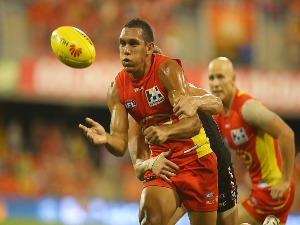 HARLEY BENNELL of the Suns handballs during the AFL match between the Gold Coast Suns and the St Kilda Saints at Metricon Stadium in Gold Coast, Australia.
