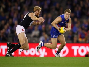 JACK MACRAE of the Bulldogsin action ahead of Andrew Phillips of the Blues during the 2018 AFL match between the Western Bulldogs and the Carlton Blues at Etihad Stadium in Melbourne, Australia.