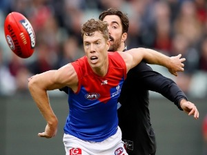 JAKE MELKSHAM of the Demons and Kade Simpson of the Blues compete for the ball during the 2018 AFL match between the Carlton Blues and the Melbourne Demons at the MCG in Melbourne, Australia.