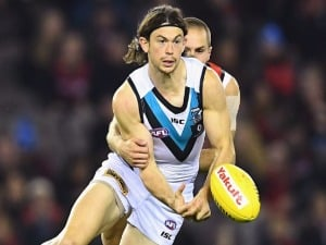 JASPER PITTARD of the Power handballs whilst being tackled David Zaharakis of the Bombers during the AFL match between the Essendon Bombers and the Port Adelaide Power at Etihad Stadium in Melbourne, Australia.