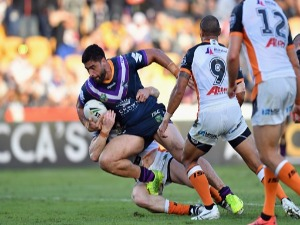JESSE BROMWICH of the Storm is tackled during the NRL match between the Wests Tigers and the Melbourne Storm at Mt Smart Stadium in Auckland, New Zealand.