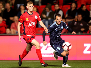 JORDAN ELSEY of Adelaide United competes with Adam Le Fondre of Sydney FC during theA-League match between Adelaide United and Sydney FC at Coopers Stadium in Adelaide, Australia.