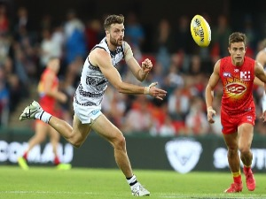 JORDAN MURDOCH of the Cats handballs during the AFL match between the Gold Coast Suns and the Geelong Cats at Metricon Stadium in Gold Coast, Australia.