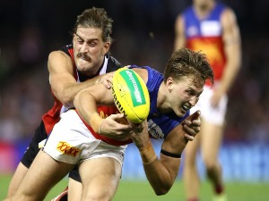 ALEX WITHERDEN of the Lions is tackled by JOSH BRUCE of the Saints during the AFL match between the St Kilda Saints and the Brisbane Lions at Etihad Stadium in Melbourne, Australia.