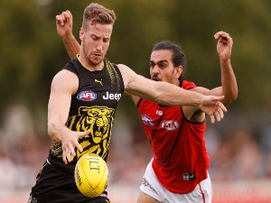 KANE LAMBERT of the Tigers kicks the ball under pressure from Jake Long of the Bombers during the AFL match at Norm Minns Oval in Wangaratta, Australia.