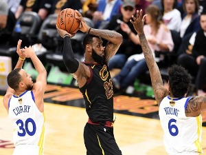 LEBRON JAMES #23 of the Cleveland Cavaliers handles the ball against STEPHEN CURRY #30 and NICK YOUNG #6 of the Golden State Warriors in the first half during Game Four of the 2018 NBA Finals at Quicken Loans Arena in Cleveland, Ohio.