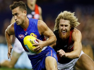 LUKE DAHLHAUS of the Bulldogs breaks awat from a Dyson Heppell of the Bombers tackle attempt during the AFL match between the Western Bulldogs and the Essendon Bombers at Etihad Stadium in Melbourne, Australia.