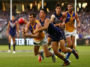 LUKE SHUEY of the Eagles gets his handball away against Bailey Banfield of the Dockers during the AFL match between the Fremantle Dockers and West Coast Eagles at Optus Stadium in Perth, Australia.