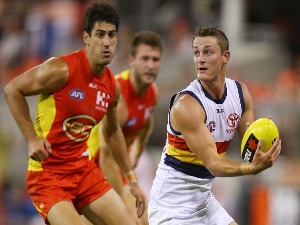 MATT CROUCH of the Crows handballs during the NAB Challenge AFL match between the Gold Coast Suns and the Adelaide Crows at Metricon Stadium in Gold Coast, Australia.