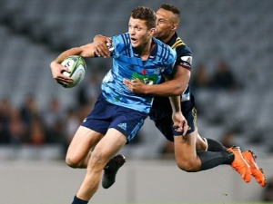 MATT DUFFIE of the Blues is tackled by Tevita Li of the Highlanders during the Super Rugby match between the Blues and the Highlanders at Eden Park in Auckland, New Zealand.