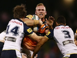 MATTHEW LODGE of the Tigers is tackled during the NRL match between the Wests Tigers and the North Queensland Cowboys at Campbelltown Sports Stadium in Sydney, Australia.