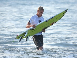 MICK FANNING of Australia returns to shore following his heat during the Australian Open of Surfing at Manly Beach in Sydney, Australia.