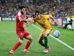 ROBBIE KRUSE of Australia is challenged by Mahmoud Al Mawas of Syria during the 2018 FIFA World Cup Asian Playoff match between the Australian Socceroos and Syria at ANZ Stadium in Sydney, Australia.