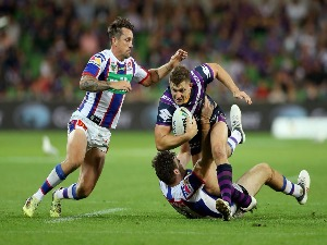 RYLEY JACKS of the Storm runs with the ball as he is tackled by the Knights defence during the round six NRL match between the Melbourne Storm and the Newcastle Knights at AAMI Park in Melbourne, Australia.