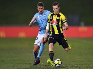 SCOTT GALLOWAY of the Phoenix controls the ball from Dario Vidosic of Melbourne City during the A-League match between the Wellington Phoenix and Melbourne City FC at QBE Stadium in Auckland, New Zealand.