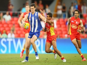 SCOTT THOMPSON of the Kangaroos kicks during the AFL match between the Gold Coast Suns and the North Melbourne Kangaroos at Metricon Stadium in Gold Coast, Australia.