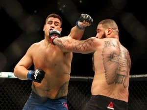 TAI TUIVASA of Australia punches Rashad Coulter of the USA in their heavyweight bout during the UFC Fight Night at Qudos Bank Arena in Sydney, Australia.