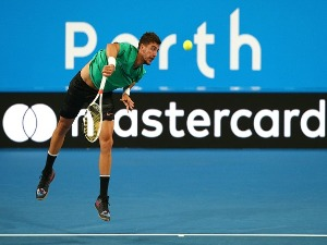 THANASI KOKKINAKIS of Australia serves in his singles match against David Goffin of Belgium in the 2018 Hopman Cup at Perth Arena in Perth, Australia.