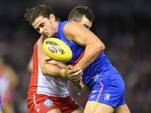 TOM BOYD of the Bulldogs handballs whilst being tackled during the AFL match between the Western Bulldogs and the Sydney Swans at Etihad Stadium in Melbourne, Australia.