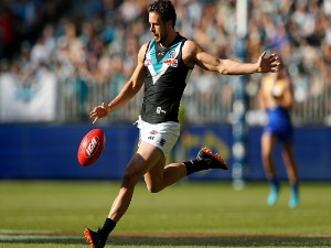 TRAVIS BOAK of the Power passes the ball during the AFL match between the West Coast Eagles and the Port Adelaide Power at Optus Stadium in Perth, Australia.