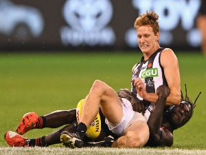 WILL HOSKIN-ELLIOTT of the Magpies kicks whilst being tackled by Anthony McDonald-Tipungwuti of the Bombers during the AFL match between the Essendon Bombers and the Collingwood Magpies in Melbourne, Australia.