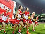 Dan Robinson of the AFL Swans run out to the field with teammates in their round one clash against the Magpies
