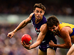 Lachie Weller of the Dockers handpasses the ball under pressure in their round 17 AFL match against the West Coast Eagles. July 16, 2017