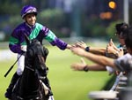 Joao Moreira celebrates with fans on the track after winning the opening race on the David Hall-trained Penzance.