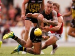 DUSTIN MARTIN of the Tigers handpasses the ball under pressure during the JLT Community Series AFL match between the Essendon Bombers and the Richmond Tigers at Norm Minns Oval in Wangaratta, Australia.