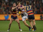 HARRIS ANDREWS of the Lions is tackled by Brad Crouch and Tom Lynch of the Crows during the 2016 AFL match between the Adelaide Crows and the Brisbane Lions at Adelaide Oval in Adelaide, Australia.