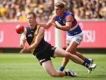 JACK RIEWOLDT of the Tigers handballs whilst being tackled by MICHAEL TALIA of the Bulldogs during the AFL match between the Richmond Tigers and the Western Bulldogs at MCG in Melbourne, Australia.