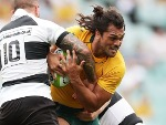 KARMICHAEL HUNT of the Wallabies is tackled during the match between the Australian Wallabies and the Barbarians at Allianz Stadium in Sydney, Australia.
