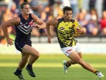 SAM LLOYD of the Tigers avoids being tackled by NATHAN FYFE of the Dockers during the AFL NAB Challenge match between the Fremantle Dockers and the Richmond Tigers at Rushton Park in Mandurah, Australia.