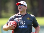 Suns coach STUART DEW smiles during a Gold Coast Suns AFL training session at Bond University AFL Field in Gold Coast, Australia.